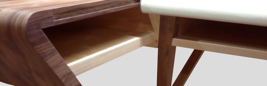 En pleine extension, ce bureau se déploie latéralement, libérant ainsi 2 espaces sur chacun de ses côtés. La partie centrale offre aussi un espace de rangement sous le plateau gainé de cuir, tandis qu'une élégante encoche allongée permet le passage d'éventuels fils à l'arrière. dimensions: h 74cm, 130x64cm matériaux: noyer français (placage et massif), sycomore (placage et massif), cuir beige, structure en multiplies de bouleau